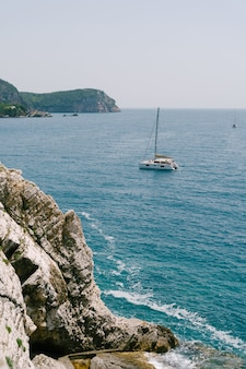 Vele di catamarano yacht a vela vicino alla costa rocciosa