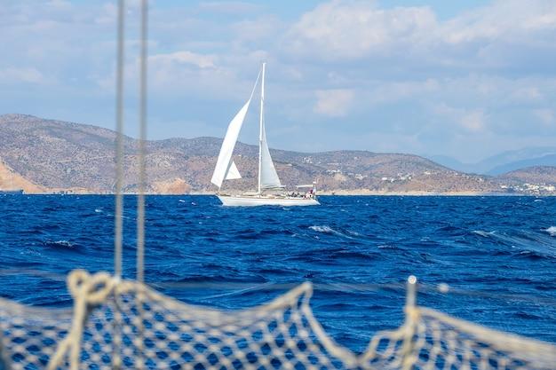 Yacht a vela sulla costa mediterranea. vista dal lato di un altro yacht. ringhiera e ragazzi fuori fuoco
