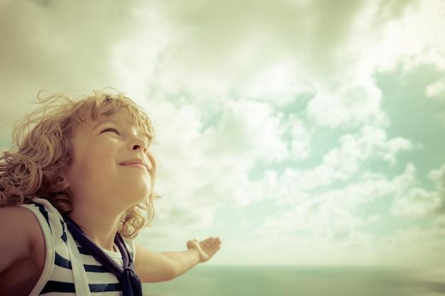 Sailor kid guardando avanti contro il cielo estivo summer