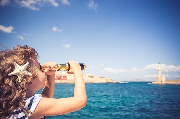 Sailor kid guardando attraverso il binocolo contro il cielo blu