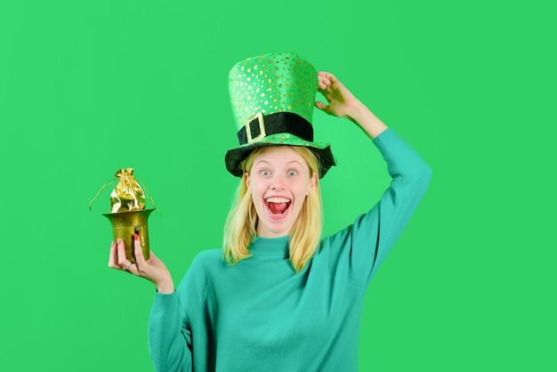 La ragazza bionda del cappello a cilindro verde del giorno di san patrizio in costume da leprechaun tiene la pentola con il leprechaun d'oro