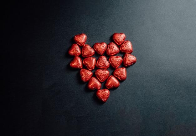 Un san valentino mock up con un cuore rosso colorato fatto di altri cuori su uno sfondo nero scuro per il giorno dell'amore con lo spazio della copia