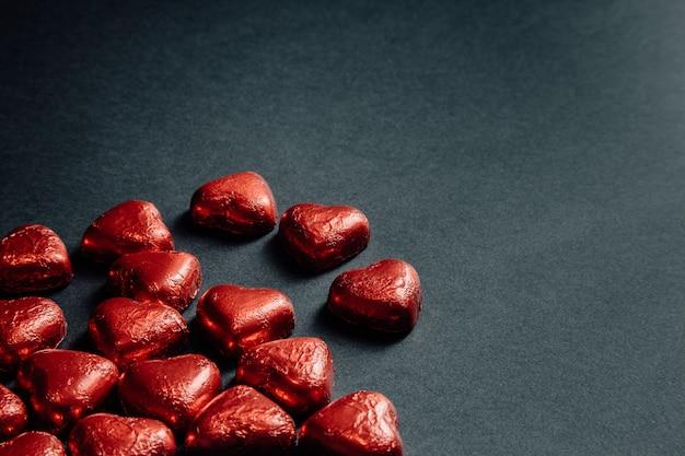 Un san valentino mock up con cuori rossi colorati su uno sfondo nero scuro per il giorno dell'amore con lo spazio della copia