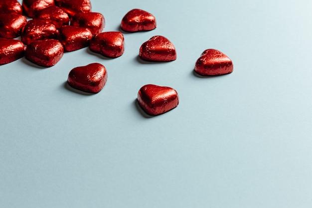 Un san valentino mock up con cuori rossi colorati su uno sfondo blu pastello per il giorno dell'amore con lo spazio della copia