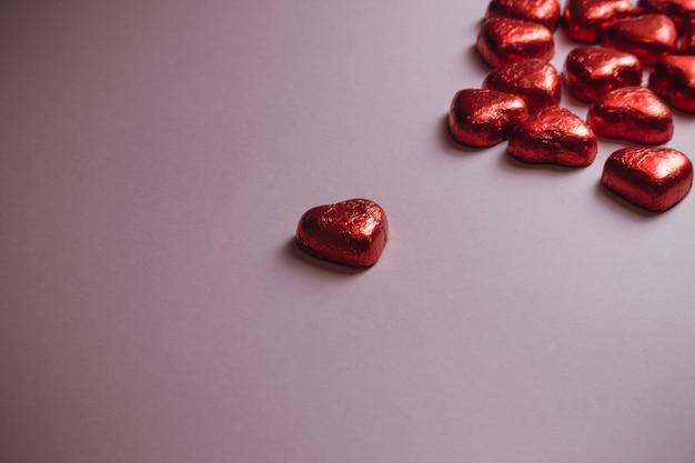 Un san valentino mock up con cuori rossi colorati su uno sfondo rosa pastello per il giorno dell'amore con lo spazio della copia