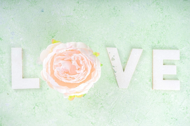 Sfondo di san valentino, biglietto di auguri o invito. lettere d'amore con fiore, vista dall'alto su flatlay sfondo verde chiaro primavera