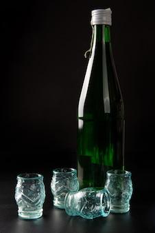 Sake, bottiglia di sake e bicchierini su superficie scura
