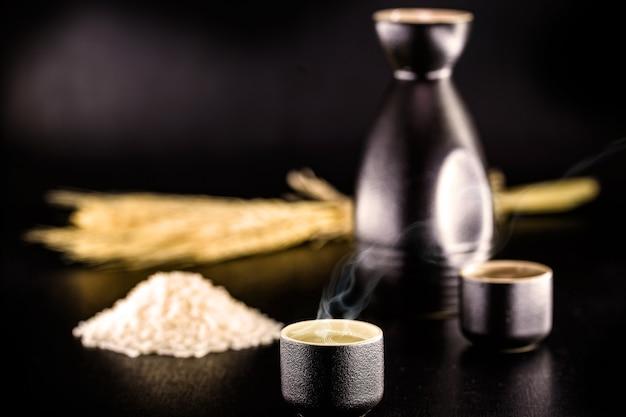 Sake o sake, bevanda distillata giapponese a base di riso, servita calda, sfondo nero e copia spazio