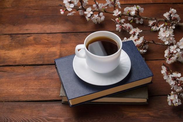 Sakura si ramifica con fiori, tazza bianca con caffè nero e due libri su una superficie di legno scuro.