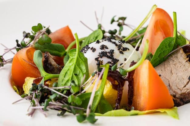 Insalata di asparagi, pomodori, carne e uovo in camicia
