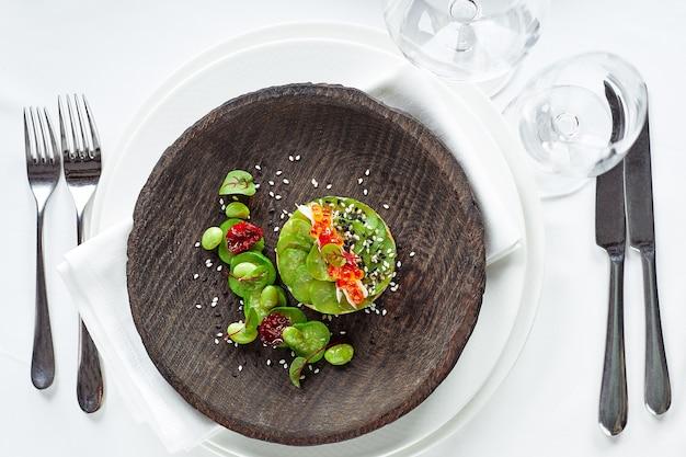 Insalata di avocado, frutti di mare, carne, verdure e semi di zucca. dietetico, sano e gustoso. piatti festivi per banchetti. menù ristorante gourmet. sfondo bianco.