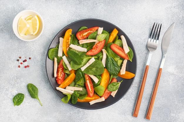 Insalata di calamari bolliti, pomodori freschi, foglie di spinaci. delizioso piatto dieta brillante con verdure e frutti di mare.
