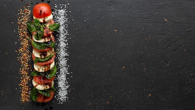 Concetto di ricetta caprese insalata su priorità bassa nera