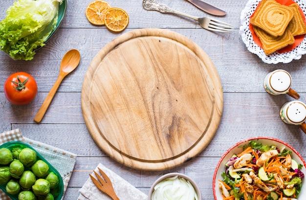 Insalata di petto di pollo con zucchine e pomodorini, su uno sfondo di legno