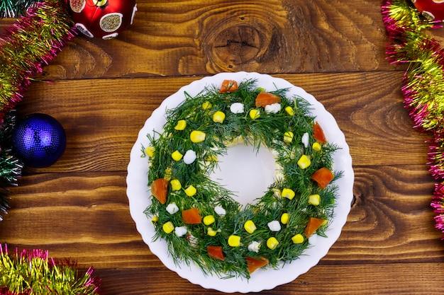 Corona di natale dell'insalata e decorazioni di natale su una tavola di legno. vista dall'alto