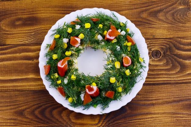 Corona di natale di insalata su un tavolo di legno. vista dall'alto