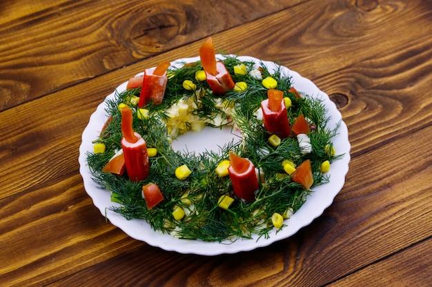 Corona di natale di insalata su un tavolo di legno