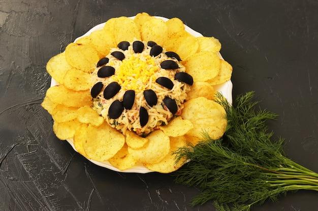 Insalata a forma di girasole, decorata con patatine fritte situate su un piatto su uno sfondo scuro