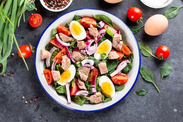 Insalata di fegato di merluzzo, uova, spinaci e pomodoro su una piastra bianca su uno sfondo scuro di ardesia, pietra o cemento