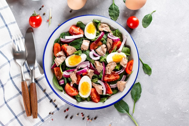 Insalata di fegato di merluzzo, uova, spinaci e pomodoro su una piastra bianca su uno sfondo di ardesia chiara, pietra o cemento