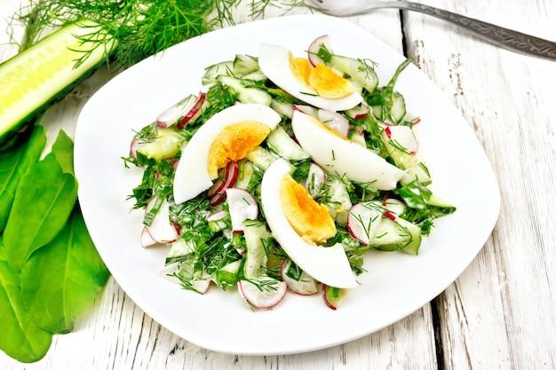 Insalata di ravanello, cetriolo, acetosa, verdure e uova, condita con maionese e panna acida in un piatto sullo sfondo di tavole di legno