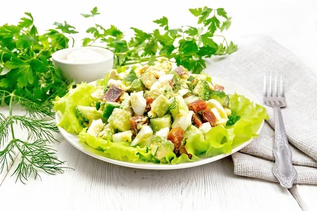 Insalata di salmone, cetriolo, uova e avocado con maionese su foglie di lattuga in un piatto, asciugamano da cucina, aneto, prezzemolo e forchetta su uno sfondo di tavola di legno