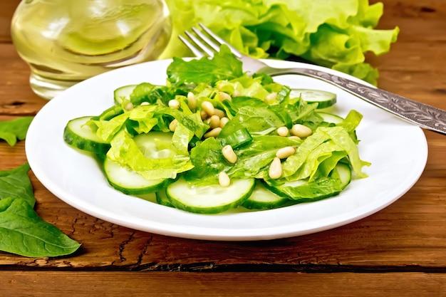 Insalata di spinaci, cetrioli freschi, insalata di rukkola, noci di cedro e cipollotti, condita con olio vegetale e una forchetta su un piatto sullo sfondo della tavola
