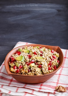 Insalata di semi di grano saraceno germogliato, avocado, noce e melograno in piatto di argilla su legno nero