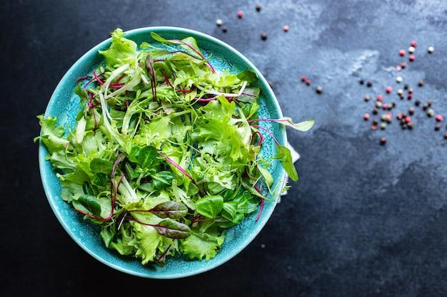 Il mix di insalata verde lascia vitamine pronte da cucinare e mangiare sul tavolo per preparare un pasto sano
