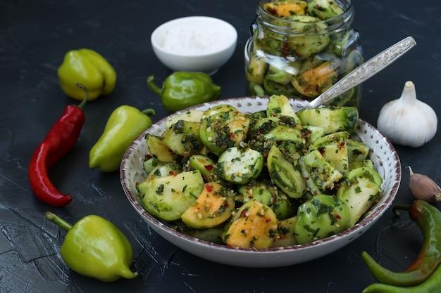 Insalata di pomodori verdi con pepe, aglio, aneto e prezzemolo su fondo grigio scuro