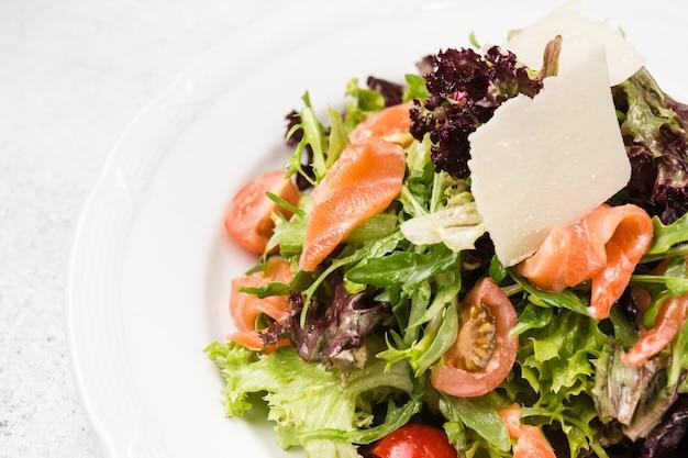 Foglie di insalata con condimento e pesce rosso