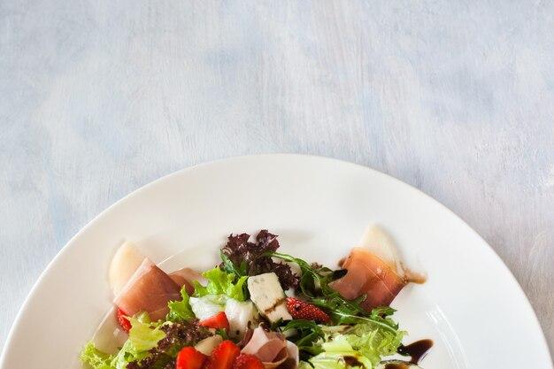 Insalata di lattuga con prosciutto di parma, formaggio blu e fragole che serve nel ristorante.