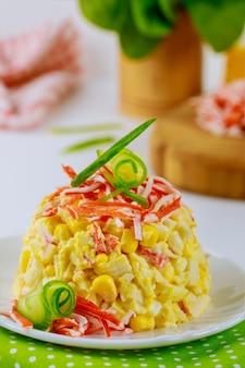 Insalata di carne di granchio, uova e mais in un piatto bianco piatto di frutti di mare