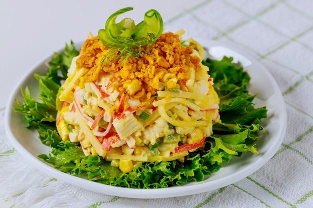 Insalata a base di polpa di granchio, uova e mais in un piatto bianco. piatto di frutti di mare.