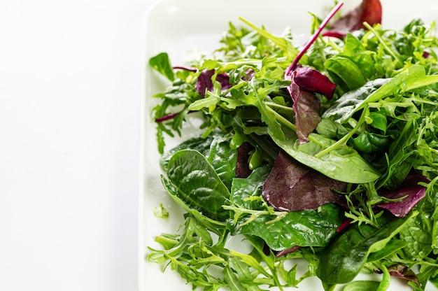 Mix di insalata di erbe fresche, rucola, bietole e spinaci in un piatto su sfondo bianco