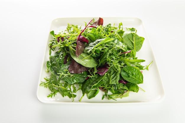 Insalata di erbe fresche, rucola, bietole, spinaci in un piatto su un piatto bianco