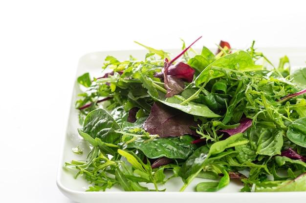 Mix di insalata di erbe fresche su un piatto bianco e uno sfondo bianco