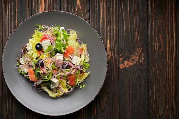 Insalata mista con salmone, formaggio feta, cipolle e olive, su un piatto, su una superficie di legno