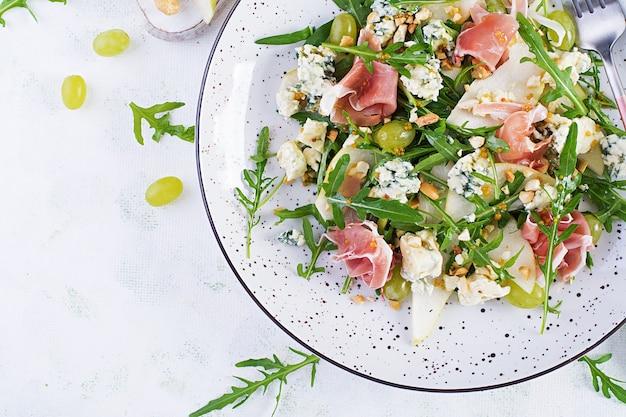 Insalata di pere, gorgonzola, uva, prosciutto, rucola e noci con salsa piccante su sfondo chiaro. mangiare sano. vista dall'alto, dall'alto