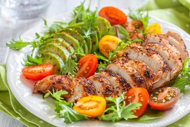 Piatto di insalata con pomodori colorati, petto di pollo e avocado