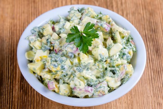 Insalata di ravanello, uovo sodo, prezzemolo e panna acida in una ciotola bianca