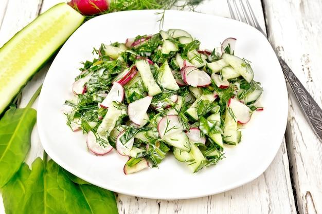 Insalata di ravanello, cetriolo, acetosa e verdure, condita con maionese in un piatto sullo sfondo di una tavola di legno chiaro