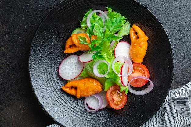 Insalata di frutti di mare verdure e chele di granchio, bastoncini di granchio surimi pomodoro, cetriolo, lattuga