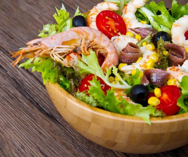 Insalata di gamberi, verdure miste, olive nere, acciughe e pomodori su fondo di legno