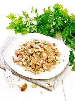 Insalata di salmone affumicato, riso, semi di girasole e zucca, mandorle, condita con miele e olio d'oliva in un piatto su asciugamano, prezzemolo e forchetta su fondo di tavola di legno chiaro