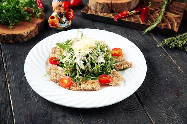 Verdure di insalata e pollo fritto in semi di sesamo
