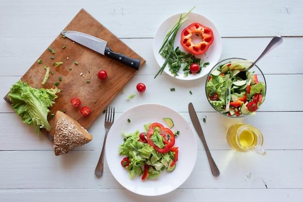 Insalata su un fondo di legno bianco da pomodori, cetrioli, lattuga e peperone. concetto di mangiare sano.