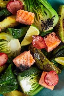 Insalata con carciofi, avocado e salmone ravvicinato, grandi segmenti di verdure carciofi avocado e cubetti di salmone fritto, primo piano, vista dall'alto