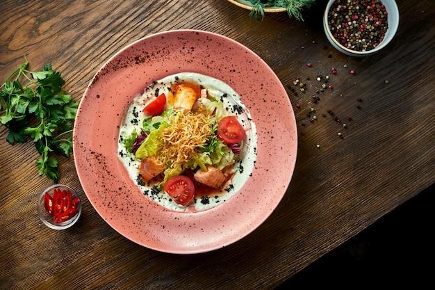 Insalata con salmone al forno, pomodorini e salsa bianca, servita in un piatto bianco. cibo del ristorante