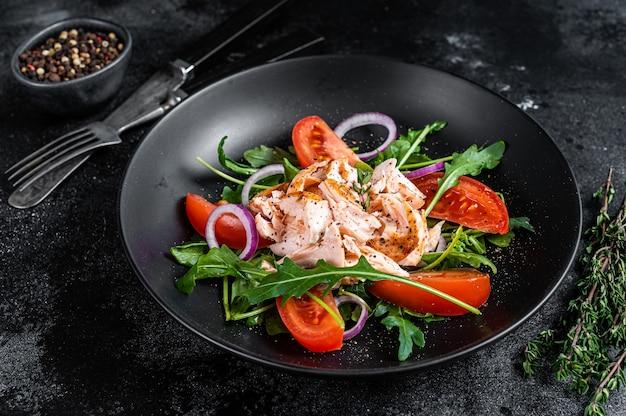 Insalata con filetto di salmone al forno, rucola fresca e pomodoro in un piatto